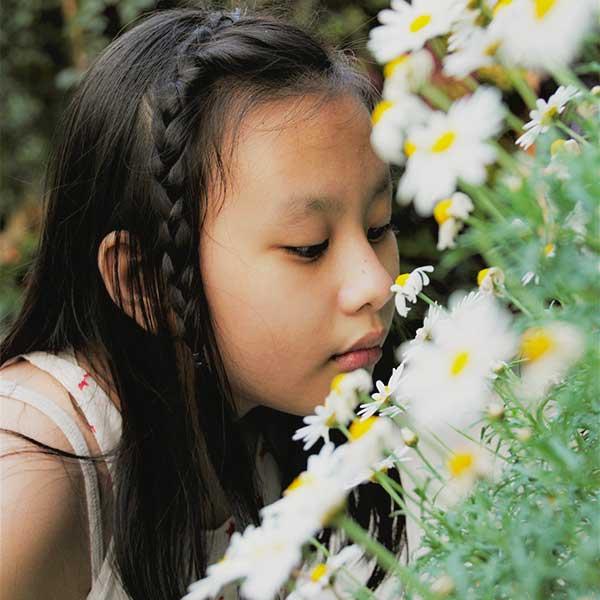 Petite fille qui sent des paquerettes.